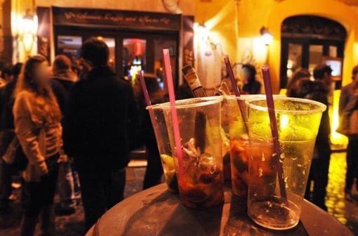 bicchieri di plastica in primo piano davanti a scene di movida in città
