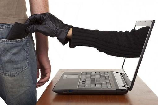 mano che sbuca da un pc per sottrarre denaro a una persona