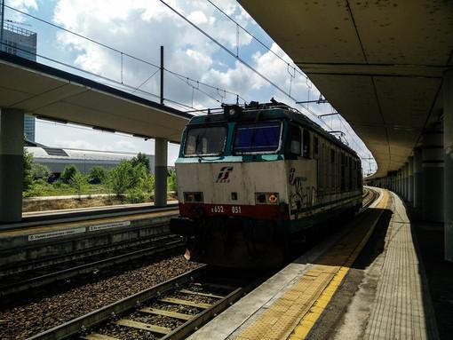 Treno in stazione con binari e banchine