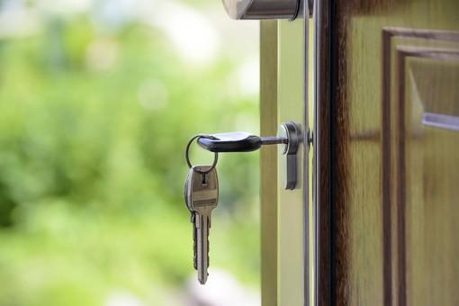 Una chiave infilata nella serratura di una porta aperta