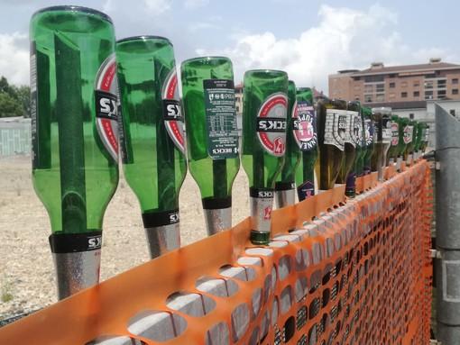 Bottiglie vuote infilate su un cancello