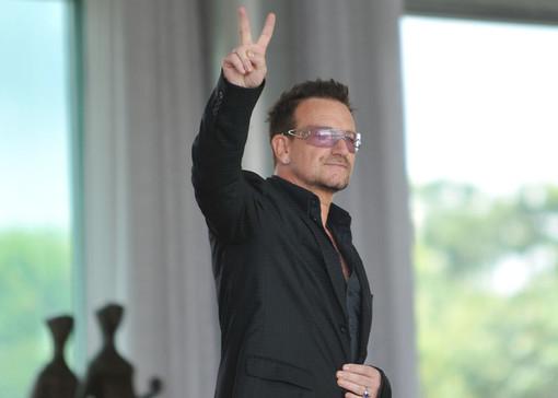 uomo con occhiali che saluta alzando il braccio e facendo il segno della V con le dita