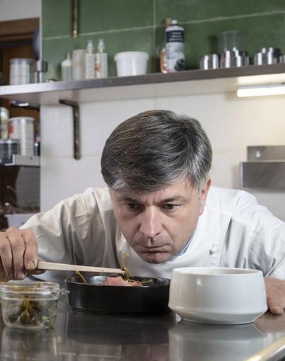 Cuoco che assaggia da una pentola con un cucchiaio di legno