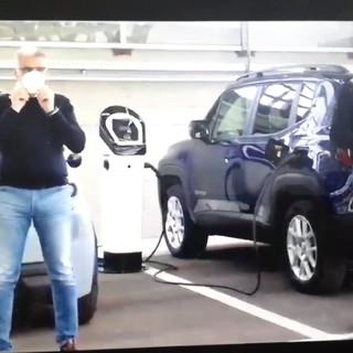 due uomini davanti a due auto elettriche
