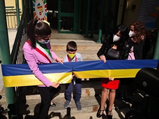 Chiara Appendino taglia nastro gialloblu con un bambino