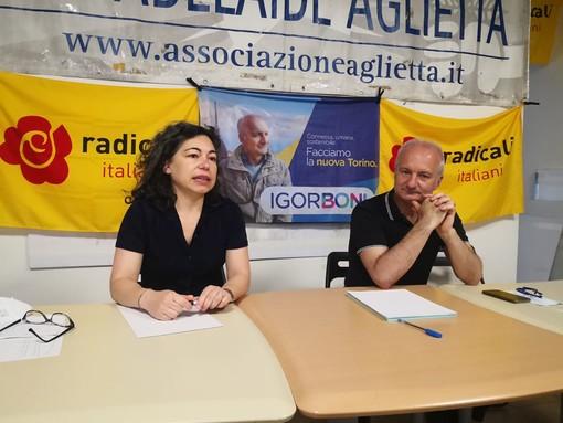 Due persone sedute a un tavolo con striscione politico alle spalle