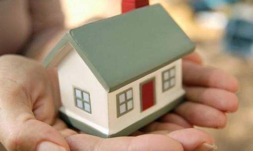 modellino di casa tenuto su un palmo di mano