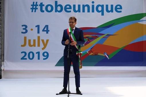 uomo con fascia tricolore che parla al microfono