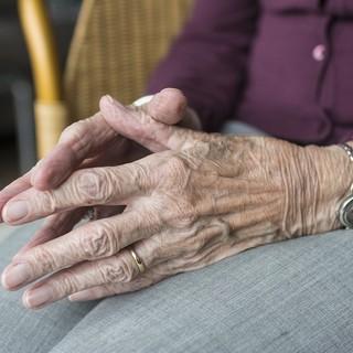 mani di una donna anziana seduta