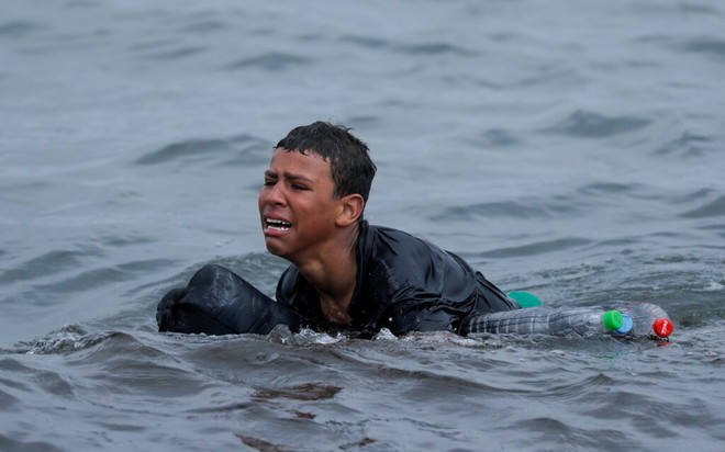 Ragazzo marocchino in mare, tenuto a galla da bottiglie di plastica - Ceuta (Spagna) 19/05/2021, Jon Nazca