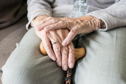 Mani di un anziano appoggiate a un bastone