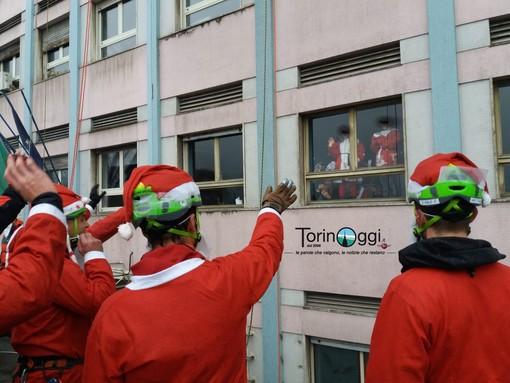 Nemmeno la pioggia ferma una solidarietà a prova di bomba: decimo raduno per i Babbi Natale sotto le finestre del Regina Margherita [FOTO e VIDEO]